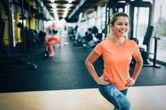 Młody uśmiechnięty sporty kobiety rozciąganie w gym Obraz Stock
