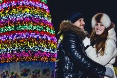 Młody uśmiechnięty szczęśliwy pary przytulenie na Bożenarodzeniowej ulicie obraz royalty free
