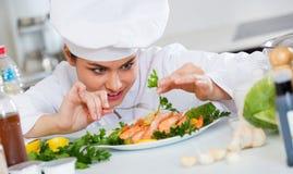 Młody uśmiechnięty szef kuchni z smażyć garnelami indoors Fotografia Stock