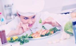 Młody uśmiechnięty szef kuchni z smażyć garnelami indoors Zdjęcie Stock
