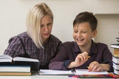 Młody uczeń angażował w lekcjach z jego nauczycielem pomaganie Fotografia Royalty Free
