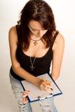 Młody uczeń bierze notatki na schowku Zdjęcia Royalty Free