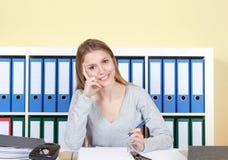 Młody uczeń przy biurową patrzeje kamerą Zdjęcia Royalty Free