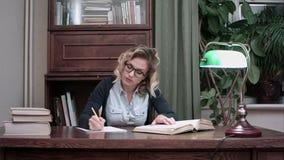 Młody uczeń siedzi przy stołem i pisze notatkach od książki w szkłach zdjęcie wideo