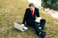 M?ody ucze? studiuje na naturze w parku blisko jeziora facet w czarnym kostiumu czerwonym krawacie i czyta laptop i obrazy stock