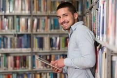 Młody uczeń Używa Jego laptop W bibliotece Zdjęcia Royalty Free