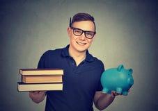 Młody uczeń z książkami i moneybox fotografia royalty free