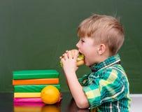 Młody uczniowski łasowanie hamburger Zdjęcia Royalty Free