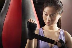 Młody ufny żeński boksera opakowanie jej nadgarstki w gym zdjęcia stock