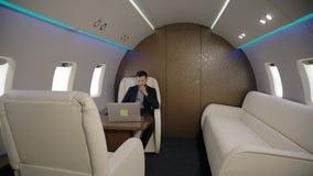 Młody ufny biznesmen pracuje z laptopu obsiadaniem w przedsiębiorcy samolotu wnętrzu zdjęcie wideo