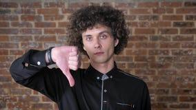 Młody ufny mężczyzna z kędzierzawego włosy seansu niechęcią i patrzeć kamerę, ściana z cegieł tło zbiory wideo