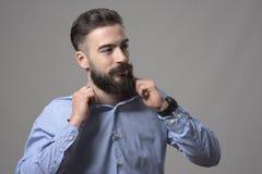 Młody ufny przystojny brodaty mądrze przypadkowy modniś przystosowywa koszulowego kołnierz patrzeje copyspace Fotografia Stock