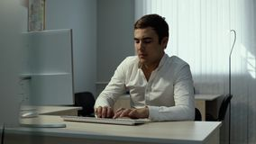 Młody urzędnik pisać na maszynie na bezprzewodowej klawiaturze zbiory