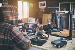 Młody vlogger mężczyzna edytorstwa wideo na laptopie i sprawdzać smartphone zdjęcie royalty free