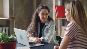 Młody właściciel mały biznes opowiada jej klient w nowożytnym biurze Kobiety siedzą przy biurkiem, gawędzenie i zbiory