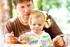 Młody w średnim wieku ojciec karmi ślicznej małej berbeć dziewczyny w restauraci Uroczy dziecka dziecka uczenie łasowanie od łyżk obraz stock