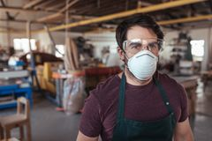 Młody woodworker stoi samotnie w jego warsztacie jest ubranym ochronną przekładnię zdjęcia stock