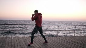 Młody wysoki mężczyzna angażował w boksować rozgrzewkowy w górę drewnianej podłogi na blisko morza Robić dodawał kroki, uderza pi zbiory