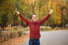 Młody z podnieceniem studencki szczęśliwy że przechodzący egzaminy Mężczyzna dźwigania ręki obrazy stock