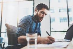 Młody zadumany mężczyzna pracuje przy pogodnym loft biurem na laptopie Biznesmen robi notatkom na papierowych dokumentów raportac Obrazy Stock