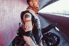 Młody zadumany rowerzysta stoi blisko jego motobike w spokojnym tunelu fotografia royalty free