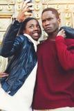 Młody zmrok skinned mężczyzna i kobiety pozuje podczas gdy fotografujący na telefon komórkowy kamerze podczas gdy stojący outdoor Zdjęcia Royalty Free