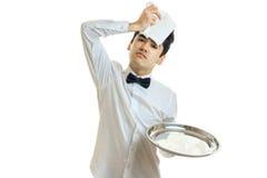 Młody znużony kelner appended kierowniczy płótno i trzymać tacę obrazy royalty free
