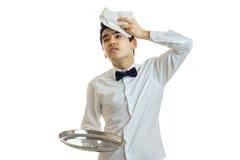 Młody znużony kelner trzyma tacę jest pusty i stawiający dalej głowa ręcznik fotografia royalty free