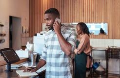 Młodych Afrykańskich przedsiębiorców ruchliwie działanie za ich kawiarnia kontuarem Zdjęcia Stock