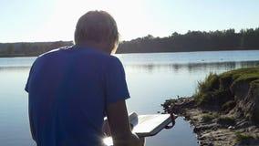 Młodych człowieków spojrzenia przy jego rodzinnym photoalbum na jeziornym banku zdjęcie wideo
