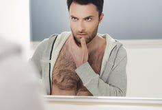 Mężczyzna spojrzenia przy on w lustrze Zdjęcia Royalty Free
