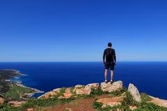 Młodych człowieków stojaki na krawędzi skały i watchs morza śródziemnomorskiego w Akamas półwysepu parku narodowym, Cypr Podróżni obrazy stock