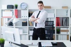 Młodych człowieków stojaki w biurze blisko stołu i składającym jego ręki na jego klatce piersiowej obraz stock