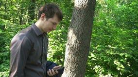 Młodych człowieków stojaki w drewnach, myśleć o coś i pracują na telefonie zbiory wideo