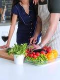 Młodych człowieków tnący warzywa i kobiety pozycja w kuchni Obraz Royalty Free