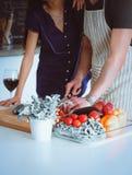 Młodych człowieków tnący warzywa i kobiety pozycja w kuchni Zdjęcie Royalty Free