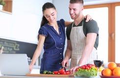 Młodych człowieków tnący warzywa i kobiety pozycja z laptopem w kuchni Zdjęcia Stock