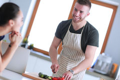 Młodych człowieków tnący warzywa i kobiety pozycja z laptopem w kuchni Obraz Stock