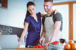 Młodych człowieków tnący warzywa i kobiety pozycja z laptopem w kuchni Obrazy Stock