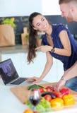 Młodych człowieków tnący warzywa i kobiety pozycja z laptopem w kuchni Obrazy Royalty Free