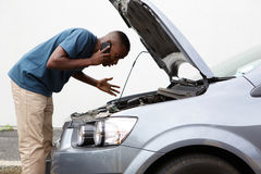 Młodych człowieków wezwania dla pomocy z poprzegradzanym samochodem obrazy royalty free