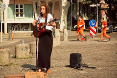 Młodych dziewczyn śpiewackie piosenki z gitarą dalej brukują ulicę Obrazy Royalty Free