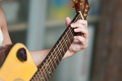 Młodych dziewczyn ręki bawić się gitarę zdjęcia stock