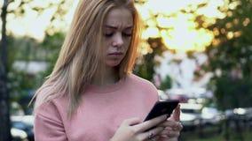 Młodych dziewczyn spojrzenia z przykrością przy smartphone ekranem zdjęcie wideo