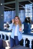 Młodych dziewczyn wzruszający szkła śmia się smartphone i utrzymuje przy uliczną kawiarnią, Obraz Stock