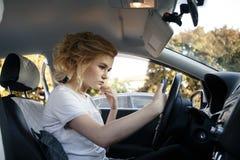 Młodych kobiet spojrzenia przy jej smartphone w samochodzie obraz tonujący obrazy stock