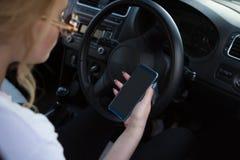 Młodych kobiet spojrzenia przy jej smartphone w samochodzie obraz tonujący obrazy royalty free