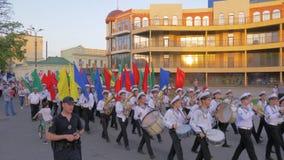 Młodych uczni akademii Morski marsz w paradzie z instrumentami muzycznymi i kolorowymi flagami wzdłuż głównej ulicy zbiory wideo