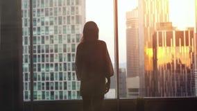 Młodzi ładni kobieta stojaki duży nadokienny przyglądającym out jej mieszkanie na miasto budynkach podczas pięknego zmierzchu zbiory