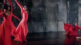 Młodzi żeńscy baletniczy tancerze tanczą przeciwu chwilowego tana w próbie w ciemnej sali, czerwone suknie kiwają zbiory